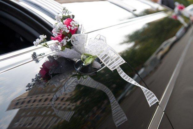 door-black-wedding-car-with-flower-ribbon_338799-1606